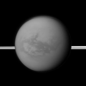 Los anillos de Saturno se ven al fondo, al tiempo que Cassini observa hacia Titán y su región oscura llamada Sangri-La, al este del sitio donde cayó la sonda Huygens. (Crédito: NASA/JPL-Caltech/Space Science Institute)