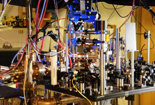 No es tu reloj normal. Átomos de iterbio son generados en un horno (cilindro de la izquierda) y enviados a una cámara al vacío (centro) para ser manipulados y utilizados por láseres en el reloj atómico QuASAR. (Crédito: NIST)